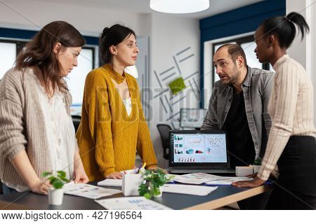 Diverse Businesspeople Communicating In Start Up Business Office Standing Over Desk Looking Through