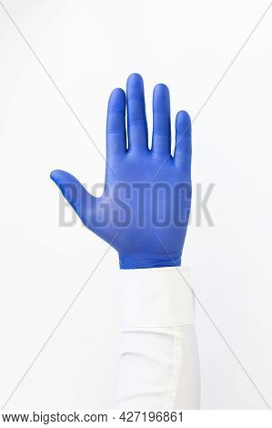 Hand In Blue Latex Glove. Stop Sign. White Background. Copy Space