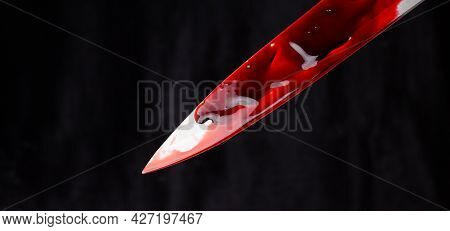 A Bloody Knife On A Black Background. The Concept Of Murder, Crime.