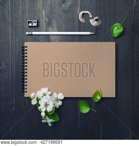 Blank Closed Sketchbook, Pencil, Sharpener And Flowers And Spring Flowers On Wood Table Background.