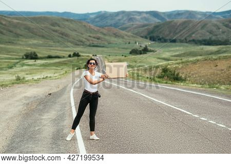 A Young Attractive Woman Hitchhiking On An Empty Road. Hitchhiking Girl. Attractive Young Woman Stan