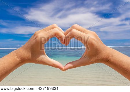 Women's Hands In The Shape Of A Heart On A Background Of Blue Sea And Sky. Love Concept