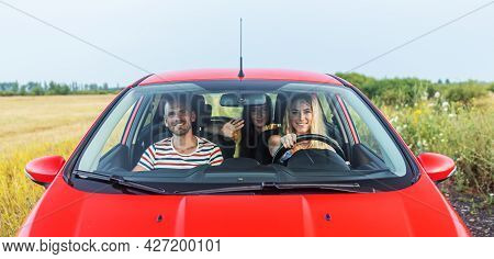 Friends In A Red Car. A Group Of Young People Travels By Car.