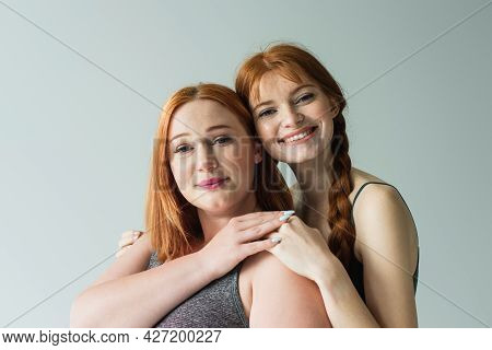 Freckled Sportswoman Hugging Plus Size Friend Isolated On Grey