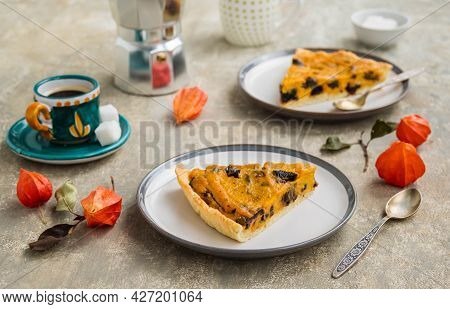 Sliced Open Pie With Pumpkin And Prunes On A Ceramic Plate On A Gray Concrete Background. Pumpkin Re