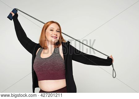 Plus Size Sportswoman Holding Skipping Rope And Looking At Camera Isolated On Grey