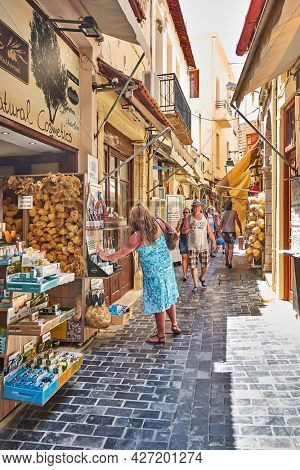 Rethymno, Crete Island, Greece - April 26, 2018: Shopping street with souvenir shops and walking people in Rethymno town