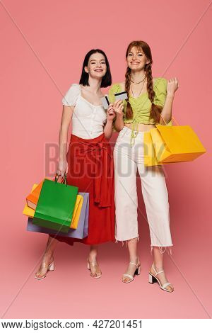 Smiling Women With Vitiligo And Freckles Holding Credit Cards And Shopping Bags On Pink Background