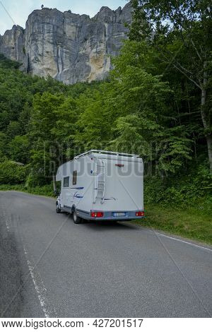 White Camper Car Driving In The Mountains. Adventurous Lifestyle. Camper Life. Travel In Mountains
