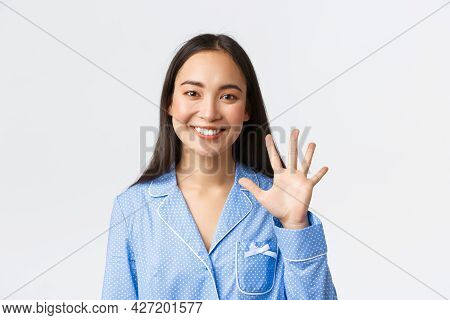 Close-up Shot Of Happy Attractive Asian Woman In Blue Pyjama Showing Five Fingers And Smiling White