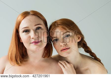 Young Freckled Woman Hugging Plus Size Friend Isolated On Grey