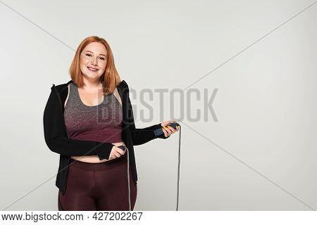 Body Positive Sportswoman Holding Jump Rope And Smiling At Camera Isolated On Grey