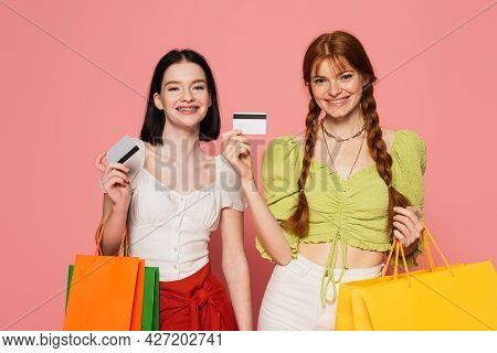 Smiling Women With Freckles And Vitiligo Showing Credit Cards And Holding Shopping Bags On Pink Back