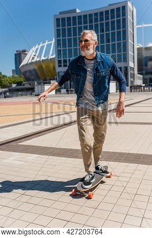 Joyful Middle Aged Man In Sunglasses Riding Longboard On Urban Street
