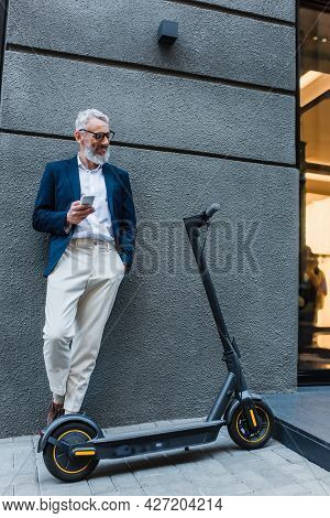 Cheerful Mature Businessman In Blazer Standing Near E-scooter And Using Smartphone