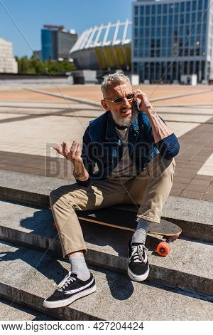 Happy Mature Man In Sunglasses Sitting On Stairs Near Longboard While Talking On Cellphone On Urban