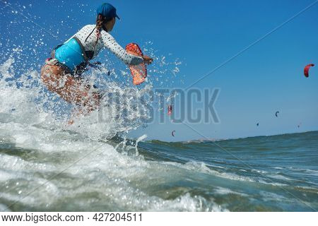 Kite surfer woman jumps with kiteboard  in transition and throws up the board