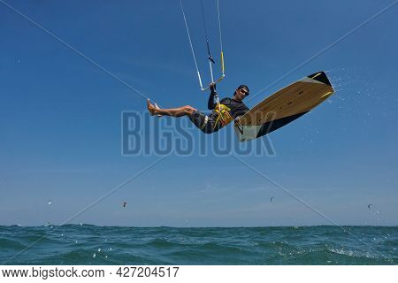 Kite surfer rjumps with kiteboard  in transition and throws up the board