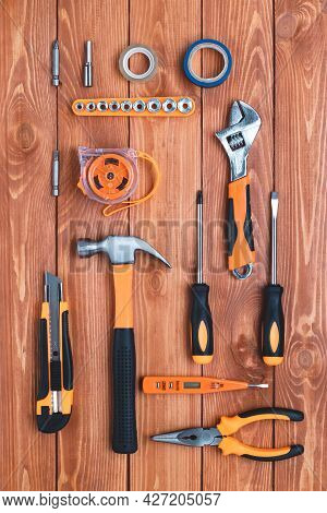 Set Of Construction Tools On A Brown Wooden Background. Hammer, Wrench, Pliers And Screwdriver. Gree