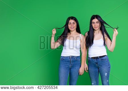 Portrait Of Two Beautiful Young Girls Of Twin Sisters With Straight Black Hair Are Playing With Thei