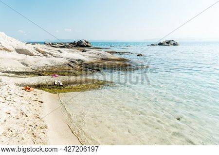 Slippers On A Beautiful Sandy And Rocky Beach, Calm Sea Waves Splashes. View Of The Sea, Ocean. Natu