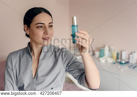 Professional Cosmetologist In Beauty Salon Showing Cream For Skincare Treatment