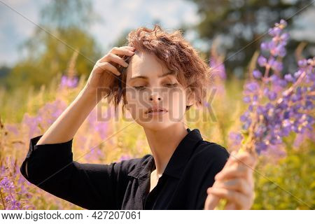 A Young Girl With A Bouquet Of Lupines In Her Hand Against The Background Of Blooming Ivan-tea On A