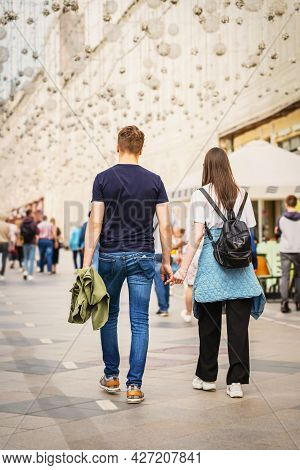 Back View Of Happy Couple Walking In City. Concept Of Modern City Life, Love. Regular People Out In