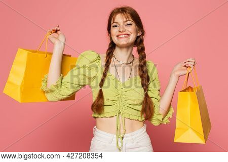 Happy Woman With Freckles On Skin Holding Shopping Bags Isolated On Pink
