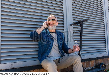 Cheerful And Mature Man In Sunglasses Talking On Smartphone And Holding Bottle Of Water Near E-scoot