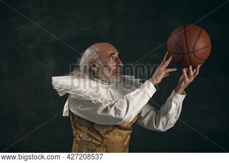 One Old Man, Actor Having Fun, Playing With Basketball Ball Isolated On Dark Vintage Background. Ret