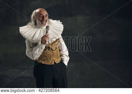 Portrait Of Elderly Gray-haired Man, Medieval Hystorical Person, Actor Singing Isolated On Dark Vint