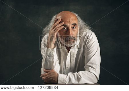 Portrait Of Old Man, Actor Looking At Camera Isolated On Dark Vintage Background. Retro Style, Compa