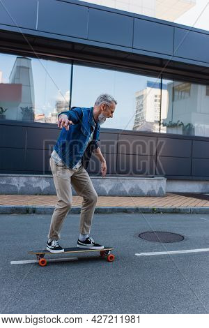 Full Length Of Amazed And Mature Man Riding Longboard On Urban Street