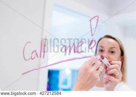 Blonde Woman Writes The Words Call Me On The Mirror With Red Lipstick.