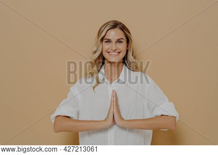Happy Cute Blond Feamle In White Shirt Pressing Palms Together In Pray, Namaste Or Saying Please Ges