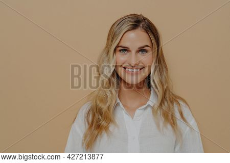 Portrait Of Calm Blonde Teenage Girl In White Shirt Smiling And Looking Straight At Camera, Wide Too