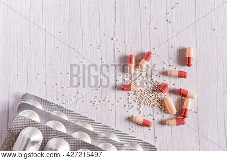 Red-white Medicine Capsules On Wooden White Table Background. Top View With Copy Space. Medicine Con