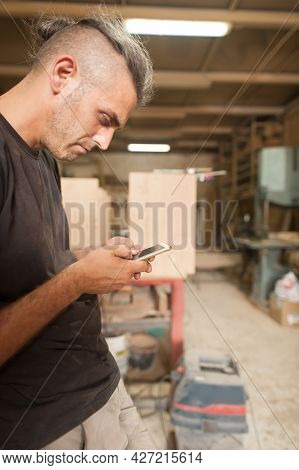 Carpenter Artisan Resting In Workshop And Scrolling On Smartphone
