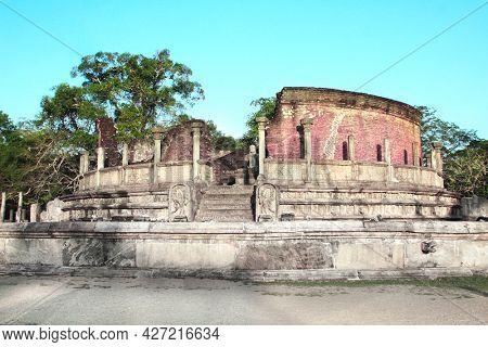 Ancient stone statue of a meditating Buddha in sunset light, Vatadage (Round House), Polonnaruwa, Sri Lanka. UNESCO world heritage site