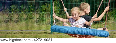 Children On A Swing. Boy And Girl Ride A Swing In The Park On A Summer Day. Swing In The Childrens A