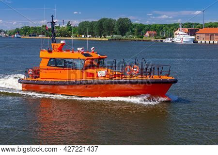 Swinoujscie. The Red Pilot Boat Goes Along The River.