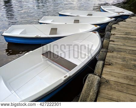 Closeup Photo Of A Few White Plastic Rowboats Moored On Wooden Dock For Fishing Or Boat Trips On A R