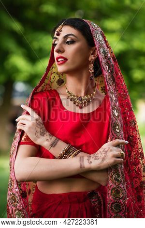 Young Indian Bride In Red Sari And Headscarf With Ornament