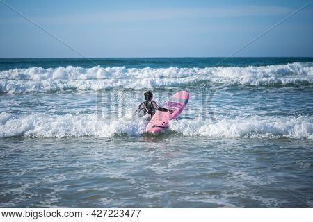 Girl With A Surfboard Overcomes The Waves. Concept: Overcoming, Determination, Incredible Beauty