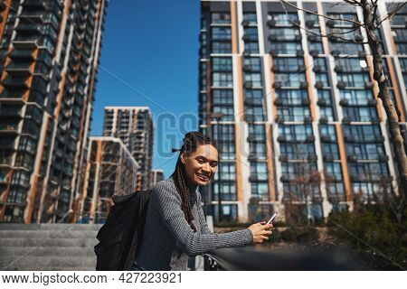 Jolly Tourist With A Backpack And A Smartphone Looking Ahead