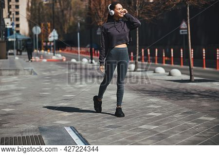Smiling Pleased Sportswoman In Wireless Headphones Talking On The Smartphone