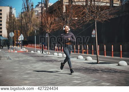 Joyous Sporty Lady Jogging To Her Favorite Music