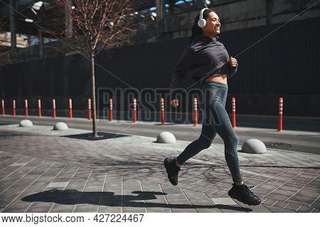 Joyful Good-looking Sportswoman Dressed In Activewear Jogging In The Morning