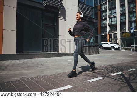 Joyous Jogger In Wireless Headphones Running To Music
